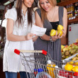 Two girls choose fruit in a supermarket — Stock Photo