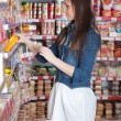Stock Photo: Girl choose food in supermarket