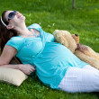 Beautiful pregnant woman relaxing on green grass — Stock Photo