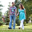 Happy couple, having joined hands walk in park — Stock Photo