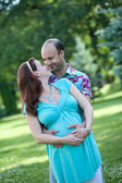 Husband with pregnant wife is resting in nature. — Stockfoto