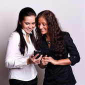 Young beautiful sisters using the cellphone to send sms — Stock Photo