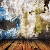 Grunge painted wall and wooden floor in a room — Stock Photo