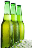 Three green beer bottles with ice isolated — Stock Photo