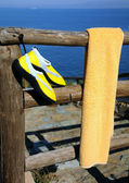 Towel and Beach Shoes on Wooden Fence — Stock Photo