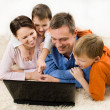 Family looking at laptop — Stock Photo