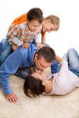 Happy family on the carpet — Stock Photo