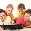 Family lying on the carpet with a laptop — Stock Photo