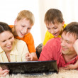 Family lying on the carpet with a laptop — Stock Photo #3209475