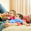 Family lying on the carpet with a laptop — Stock Photo #3209499