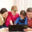 Family lying on the carpet with a laptop — Stock Photo #3209508