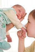 Boy kissing a newborn sister's hand — Stock Photo