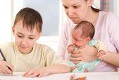 мальчик рисует с его матерью и новорожденным — Стоковое фото