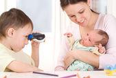 Boy looking through binoculars at the newborn — Stock Photo