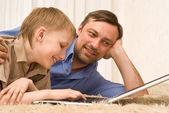 父亲和儿子在地毯上用的笔记本电脑 — 图库照片