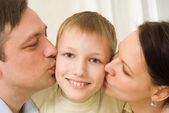 Parents kissing her child — Stock Photo