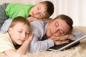 Father sleeps with sons on a laptop — Stock Photo