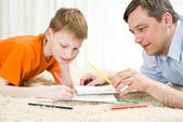 Father and son lying and draw — Stock Photo