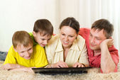 Family lying on the carpet with a laptop — 图库照片