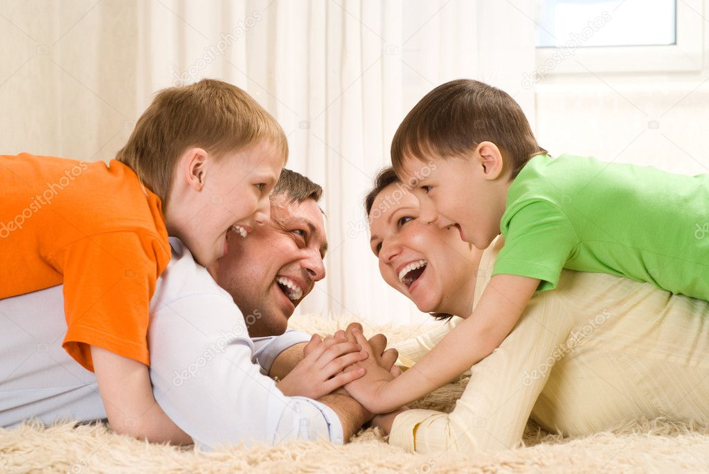 Happy parents are on the carpet with his two sons — Stock Photo #3208993