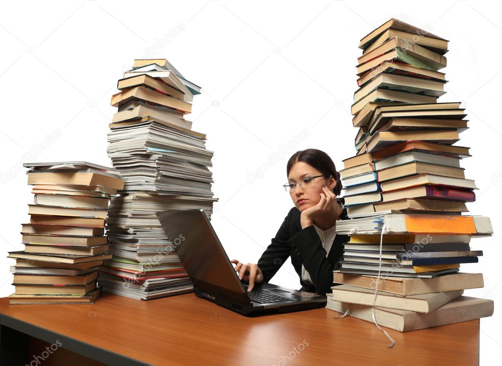 She works with the computer (a lot of books on the table)  Stock Photo #3038846