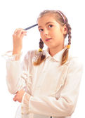 Schoolgirl holds a pen at a forehead — Stock Photo