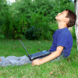 Boy with notebook sit at tree outdoors — Stock Photo