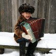 Boy with accordion under snowfall — Stock Photo #2732625