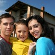 Family beside their new house — Stock Photo