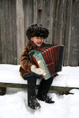 Boy with accordion under snowfall — Stock Photo