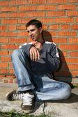 Uomo con apple accanto al muro di mattoni — Foto Stock