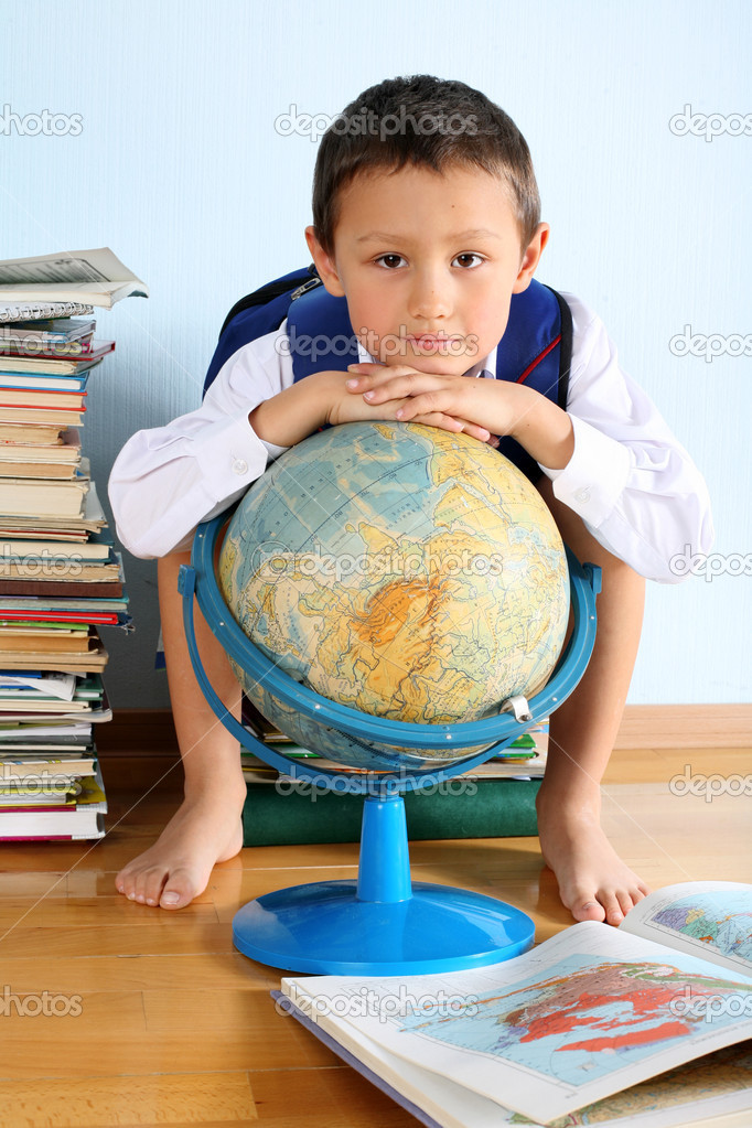 Schoolboy sitting on the heap of books with globe — Stock Photo #2732233