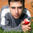 Man in green grass with apple — Stock Photo