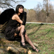 Black angel outdoors — Stock Photo