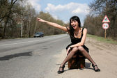 Hitch-hike girl with vintage suitcase — Stock Photo