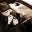 Stock Photo: Man in car with cigar and rifle