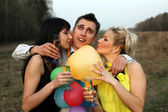 Two girl with wine kissing man outdoors — Foto de Stock