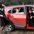 Two girls, car and man with rifle — Stock Photo