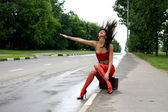 Hitch-hiking girl in the road — Stock Photo