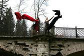 Girls in fall park in old bridge — Stock Photo