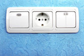 Electrical switch and plug in blue wall — Stock Photo