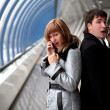 Man and woman speaking phones inside bridge — Stock Photo
