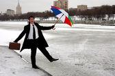 Businessman with umbrella in winter city — Stock Photo