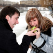 Girl and man outdoors with apple — Stock Photo #2861664