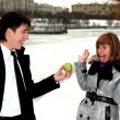 Girl and man outdoors with apple — Stock Photo