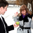 Girl and man outdoors with apple — Stock Photo #2861985