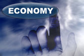 Hand and button with word of ECONOMY — Stock Photo