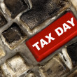 Red Tax Day key on a burned computer keyboard - Stock Photo
