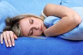 青いソファーで眠っている若い女性 — ストック写真