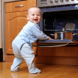 Funny baby cooking at stove — Stock Photo